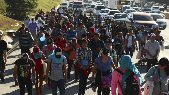 Migrants traveling in a group begin their journey toward the U.S. border as they walk along a highway in San Salvador, El Salvador, early Jan. 16, 2019. Migrants fleeing Central America's Northern Triangle region comprising Honduras, El Salvador and Guatemala routinely cite poverty and rampant gang violence as their motivation for leaving.