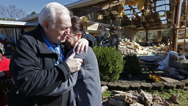 Pastor Steve Blaylock, left, comforts his wife Pat Blaylock amid the rubble that was once the First Pentecostal Church in Columbus, Miss., Feb. 24, 2019. A tornado Saturday wrecked havoc in the community, destroying a number of businesses as well as damaging and destroying homes.