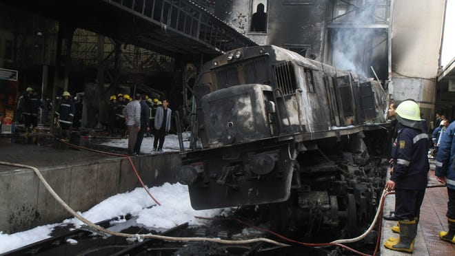 Firefighters and onlookers gather at the scene of a fiery train crash at the Egyptian capital Cairo's main railway station on Feb. 27, 2019.