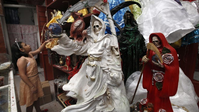 """In this Feb. 19, 2017 file photo, a child arranges statues of La Santa Muerte, or """"Our Lady of Holy Death,"""" on the edge of Mexico City's Tepito neighborhood."""