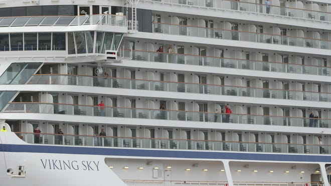 Some of the remaining passengers look out as the cruise ship Viking Sky arrives at port off Molde, Norway, Sunday March 24, 2019, after having problems and issuing a Mayday call on Saturday in heavy seas off Norway's western coast. Rescue helicopters took more than 475 passengers from a cruise ship that got stranded off Norway's western coast in bad weather before the vessel departed for a nearby port under escort and with nearly 900 people still on board, the ship's owner said Sunday.