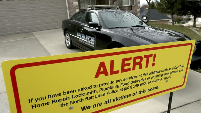 A warning sign and a police officer's vehicle are stationed at Walt Gilmore's home on Thursday, March 21, 2019. The Utah family has become the victim of extreme stalking involving unwanted service providers repeatedly being sent to their home, according to the homeowner and police.