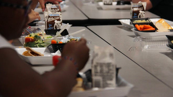 """Students eat lunch at Lincoln Elementary School in September 2019. Schools across Oklahoma will be closed until at least April 6, but schools that take part in summer meal programs will be allowed to prepare """"grab and go"""" meals to students during the closure."""