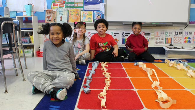 Students show off their paper chains. The yellow chain was their first attempt and the blue chain was their second attempt.