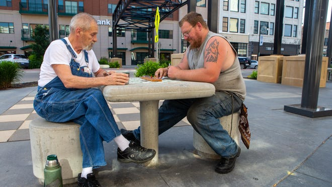 "Joking while they play, Harold Truhe, left, and  Danny Dennis, right, share a table to play cribbage Monday afternoon off Kansas Ave. in downtown Topeka. ""Checkers is to chess as bridge is to cribbage,"" Truhe said."