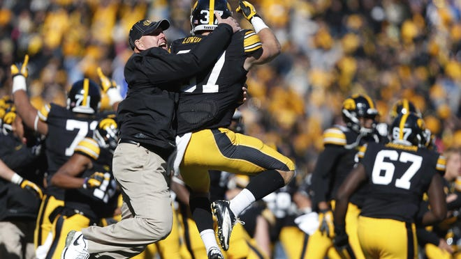 """FILE - In this Oct. 26, 2013, file photo, Iowa strength and conditioning coach Chris Doyle, front left, celebrates with defensive back John Lowdermilk (37) following their win in overtime against Northwestern in an NCAA college football game  in Iowa City, Iowa. Iowa football strength and conditioning coach Doyle has been placed on administrative leave after several black former players posted on social media about what they described as systemic racism in the program.Head coach Kirk Ferentz made the announcement Saturday, June 6, 2020, calling it """"a defining moment†for Iowa's football program in a video posted on the team's Twitter account."""