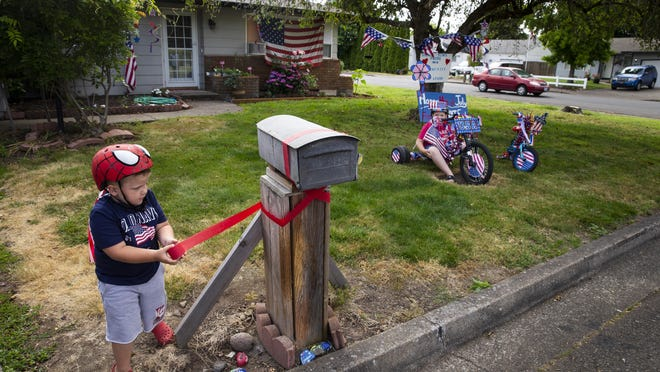 Four-year-old Hunter Holt, left, decorates his family's mailbox for the 4th of July while his brother Landon, 9, waits for the judges to drive by for a visit during Harrisburg July 4th Reverse Parade Saturday. [Chris Pietsch/The Register-Guard] - register-guard.com