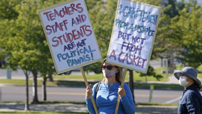 A teacher attends a demonstration over schools reopening.