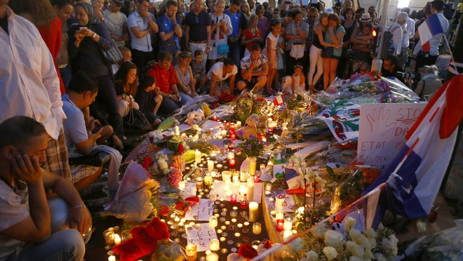 People gather at a makeshift memorial to honor the victims of an attack near the area where a truck mowed through revelers in Nice, southern France, on July 15, 2016. A large truck mowed through revelers gathered for Bastille Day fireworks in Nice, killing more than 80 people and sending people fleeing into the sea as it bore down for more than a mile along the Riviera city's famed waterfront promenade.