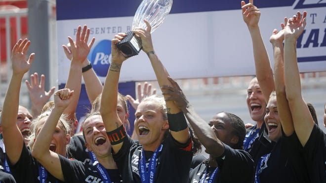 Houston Dash forward Rachel Daly holds the trophy alongside teammates while celebrating their Challenge Cup championship win against the Chicago Red Stars on Sunday in Sandy, Utah.
