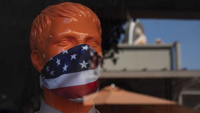 """A mannequin wears a face mask at the Citadel Outlets in Commerce, Calif., Thursday, July 2, 2020. California Gov. Gavin Newsom on Thursday urged Californians to turn to their """"better angels"""" and use common sense over the holiday weekend by wearing a mask and skipping traditional gatherings with family and friends."""