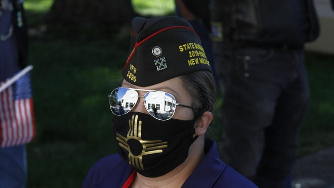Victoria Haddox, 33, of Rio Rancho, looks at the shuttered entrance of New Mexico state capitol Wednesday, June 24, 2020, in Santa Fe, New Mexico. Haddox, of Veterans of Foreign Wars Post 5890, was among a crowd of 20 members of private clubs and fraternal orders who gathered to urge the governor to lift their organizations from a COVID-19 closure order.