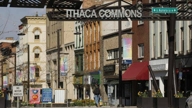 In this April 15, 2020 photo, a lone pedestrian makes their way through the Ithaca Commons in Ithaca, N.Y. Most of the almost 24,000 students at Cornell University and 6,200 more from Ithaca College effectively vanished in March when the pandemic struck, leaving behind struggling restaurants and shops. Locals still reeling from the outbreak and resulting exodus are wondering when - or if - things will get back to normal.