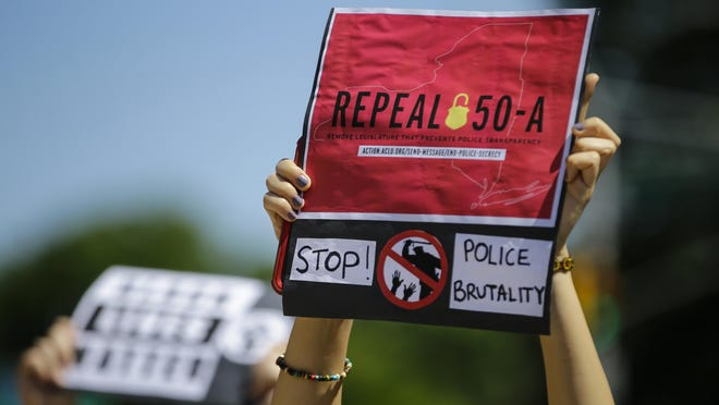 FILE-In this June 8, 2020 file photo, a protester holds a sign outside Queens County Criminal Court calling for the repeal of section 50-a, a law prohibiting the public release of police officer disciplinary records. With scores of disciplinary records already online, Judge Katherine Polk Failla said on Friday, Aug. 21, 2020, that she is lifting a temporary restraining order that had barred New York City's police watchdog agency, police department and other entities from making such information public.
