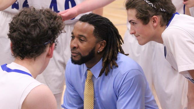 Coventry boys basketball coach Devon McAfee talks to his players on the bench during a game last season.