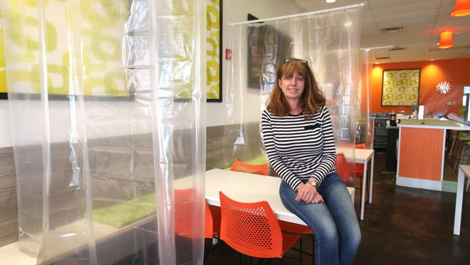 Kim Shapiro, co-owner of Twisted Citrus, at her restaurant in North Canton on May 7. The owners had reconfigured seating and hung clear plastic shower curtains between tables for coronavirus protection.