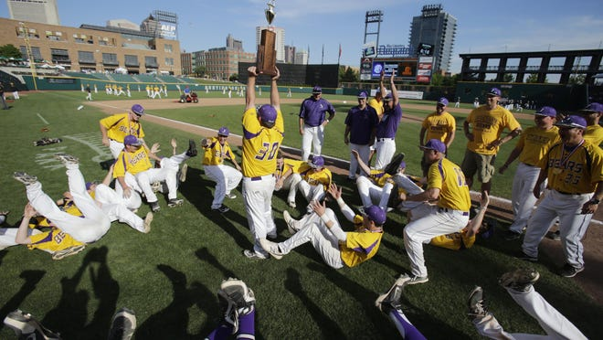 The 2014 Jackson Polar Bears celebrate winning the Division I state championship as senior Zach Dickens raises the trophy.