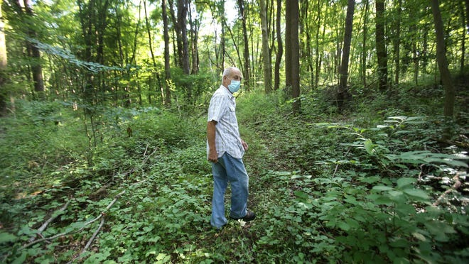 Carl Dorn walks on his property in Lawrence Township. He inherited 157 acres that developers offered to buy for $1 million. He declined and is working with Western Reserve Conservancy District to make sure it remains a nature setting forever.