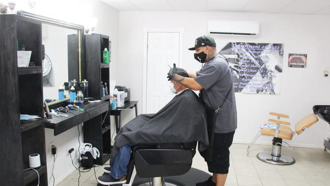 George Vasquez of Department of Cuts gives a haircut to a customer.
