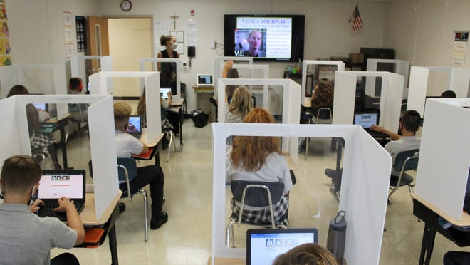 Pope John XXIII Middle School seventh-grade students listen to a video journal at their desks during their science class with Kristin VanBenschoten Thursday, Sept. 3.