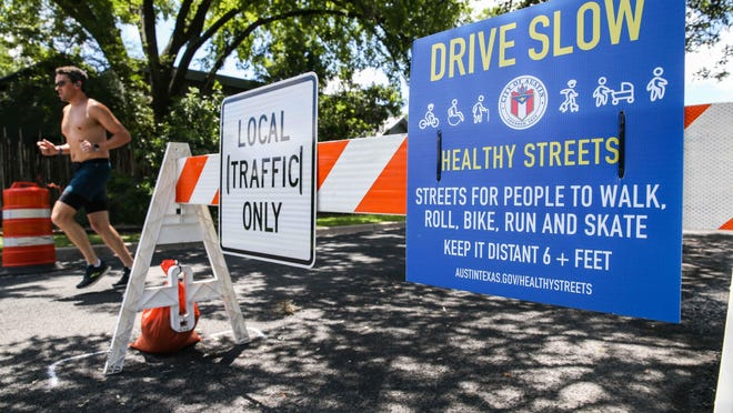 A jogger uses the Bouldin Avenue closed by the City of Austin as part of the iniciative to create more space to allow for physical exercise for residents to walk and play in Austin on May 26.