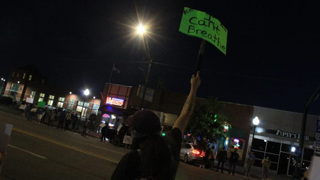 Daniel Springs displays a sign on Sunday, May 31, 2020, at the intersection of 10th Street and Garrison Avenue during a Black Lives Matter protest in Fort Smith.