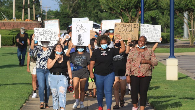 Demonstrators march to the University of Arkansas Fort Smith bell tower on Friday, June 26, 2020, during a protest against racism at UAFS.