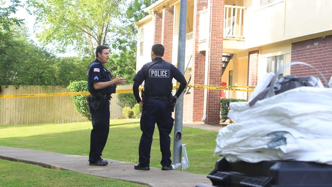 Fort Smith police Cpl. Randy Triplett, left, speaks to officer Alex Meza at the scene of a homicide investigation on Tuesday, June 2, 2020 at Pike Place Apartments.
