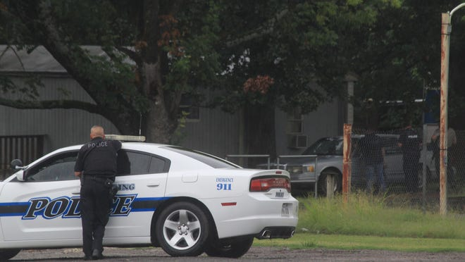 A Barling police officer watches as police and Sebastian County sheriff's deputies approach a residence during a standoff with a barricaded man on Wednesday, Aug. 26, 2020, on H Street in Barling.