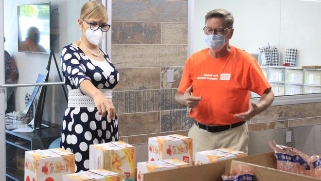 Feeding America CEO Claire Babineaux-Fontenot, left, eyes boxes off food as Antioch For Youth & Family Marketing Director Ken Kupchick gives her a tour on Friday, Aug. 21, 2020, at the Antioch food pantry in Fort Smith.