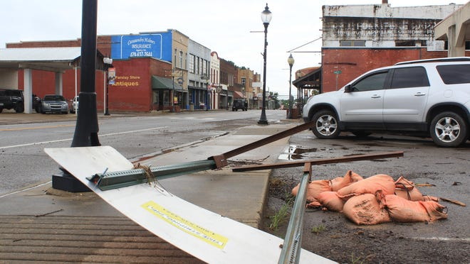 A sign lies fallen next to a pile of sandbags on Main Street on Wednesday, Aug. 2, 2020, in downtown Waldron.