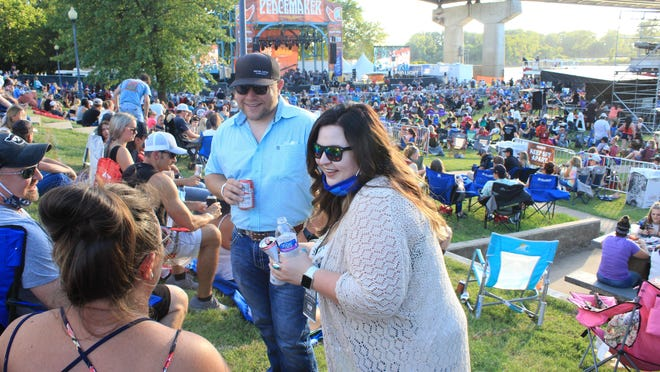 Christine Taylor of Fort Smith, right, and Jeff Hester of Hartford, center-right, speak to Rhianna Wagoner, center-left, and Clay Wagoner of Greenwood on July 24 at Peacemaker Festival in Fort Smith.