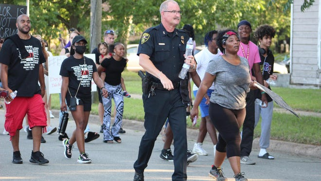 Denison Police Chief Mike Gudgel walks with protesters during a march in support of George Floyd in Denison in 2020.