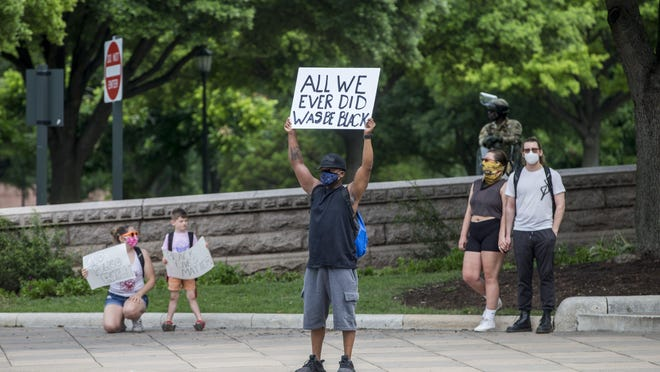 Steve Smith holds a sign in protest outside the Capitol grounds in Austin on May 31.