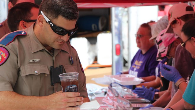 Department of Public Safety trooper John Hoy carries his lunch and drink as North Lake Community Church members serve lunch to other law enforcment officers Tuesday in the parking lot of the Law Enforcement Center.