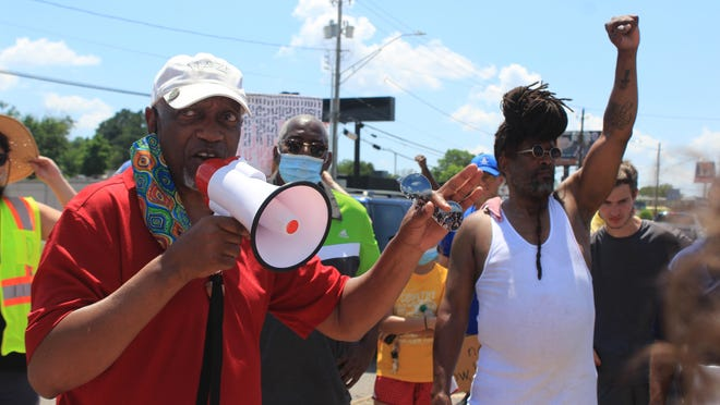 Fort Smith Mayor George McGill, left, gives a speech as demonstrator Asad Muhammad raises his fist on Saturday, June 6, 2020, during a Black Lives Matter protest on the northwest corner of Zero Street and Jenny Lind Road.