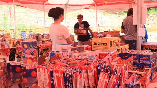 Cindy Fisk, center, carries a load of fireworks at Hale's Fireworks stand on Friday, July 3, 2020, in Greenwood.