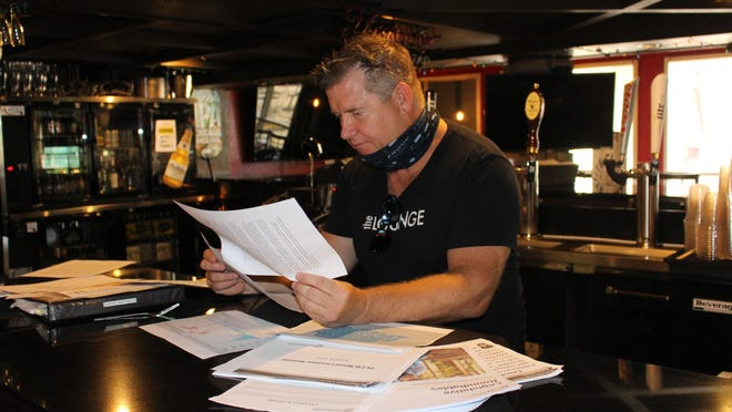 Steve Ertle, manager of The Lounge at Baymont Inn in Stroudsburg, pores over a stack of COVID-19 regulations, facts and figures at the bar. Despite low case counts and few coronavirus-related incidents in the Poconos' restaurant industry, owners and operators will have to adhere to an as-yet-unspecified set of rules to return to 50% capacity limits later this month.
