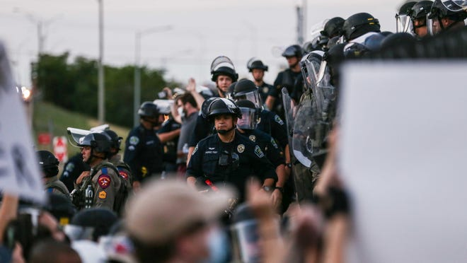 Austin police officers on Thursday protect the Interstate 35 crossing near Austin police headquarters, where protesters decried the death of George Floyd, police brutality and racism in Austin.