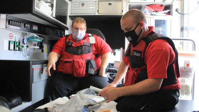 Fort Smith EMT Scott Schmitt, left, and Paramedic Supervisor Tim Mounts observe equipment in August. 2020. EMTs will soon be able to administer medication from the patient instead of waiting until reaching the hospital.