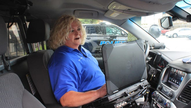 Crisis Intervention officer Cheri Taylor looks at the computer inside a patrol cruiser on Friday, Aug. 14, 2020, at the Fort Smith Police Department.