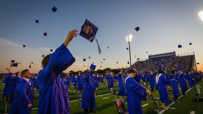 Members of Van Alstyne High School's class of 2020 toss their graduation caps into the air.