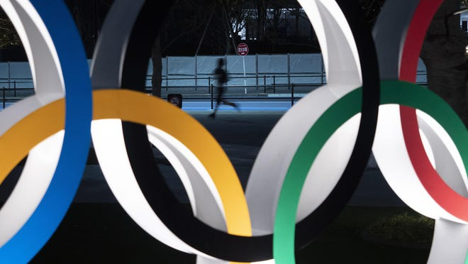 In this March 30, 2020, file photo, a man jogs past the Olympic rings in Tokyo. The head organizer for the 2028 Summer Games in Los Angeles has asked Olympic leaders for a rule change that would allow athletes to protest against racism either from the podium or at other times during the international competition.