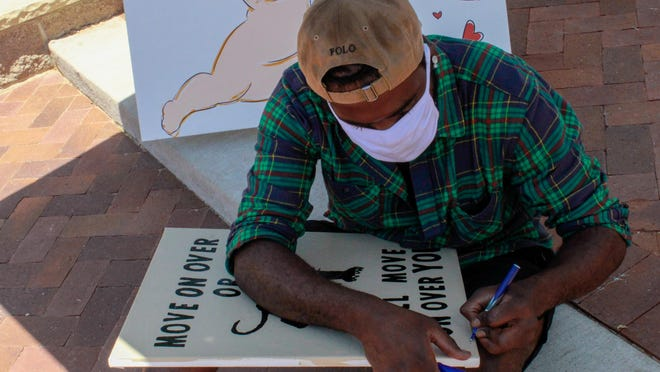 Rexon Mosley Jr. signs a piece of his artwork that he sold at the Juneteenth event in Lubbock.