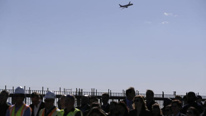 A plane flies over a topping out ceremony in front of the new Terminal 1 at Newark Liberty International Airport in Newark, N.J., Wednesday, Oct. 23, 2019.