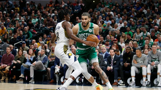 Boston forward Jayson Tatum drives to the basket against Indiana guard Justin Holiday during their March 10 game -- their last before the coronavirus halted the season. Celtics games will resume on July 31 in Walt Disney World.