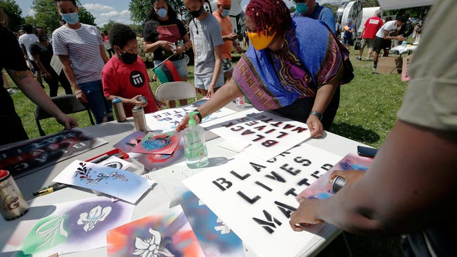 People create signs and artwork during a Juneteenth rally on Friday in Boston. Juneteenth commemorates when the last enslaved African Americans learned they were free 155 years ago.