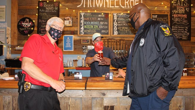 ShawneeCraft Brewing Company CEO Michael Albert serves up a pint of Blue and Black, a blonde ale conditioned on 50 pounds of blueberries and 50 pounds of blackberries, to Monroe County United President Thomas Jones as East Stroudsburg University's Chief of Police Bill Parrish hangs out at the bar. For each pint of the brew sold, ShawneeCraft will donate $1 to support MCU's Police Town Hal forum series, which aims to improve relationships between local law enforcement and the surrounding community.