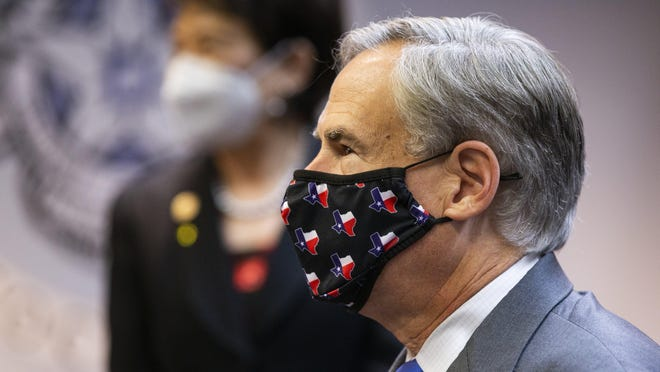 "Gov. Greg Abbott waits Thursday as elected officials sign a ""Back the Blue"" pledge after a press conference where he announced proposals to crack down on rioters."