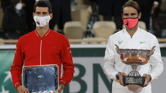 Rafael Nadal, right, holds the trophy as he celebrates winning the French Open against Novak Djokovic, left, on Sunday.